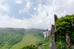 Jeunes couples dans l'amour, appréciant leur voyage dans les montagnes Vue de côté avec de grandes belles montagnes dans le premi Photos libres de droits