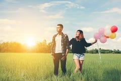 Jeunes couples dans l'amour avec des ballons dans des mains dans l'herbe verte b Photo libre de droits