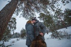 Jeunes couples dans l'amour avec le chien marchant dans la forêt et les baisers neigeux de pin Image libre de droits