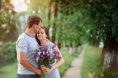 Jeunes couples dans l'amour avec un bouquet des fleurs sur un fond du chemin Images stock