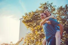 Jeunes couples dans l'amour ayant le jardin de floraison d'amusement au printemps La femme monte sur son ` s d'ami de retour au c Image stock