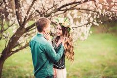 Jeunes couples dans l'amour ayant une date sous les arbres roses de fleur Photos libres de droits
