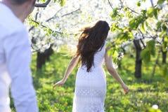 Jeunes couples dans l'amour courant au printemps le jardin de fleur Photographie stock libre de droits