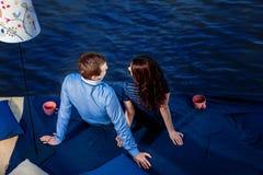 Jeunes couples dans l'amour détendant sur la terrasse près de l'eau Photos libres de droits