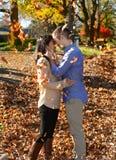Jeunes couples dans l'amour dans un arrangement d'automne avec les feuilles AR en baisse images libres de droits