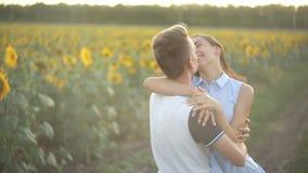 Jeunes couples dans l'amour dansant le soir au coucher du soleil dans un domaine des tournesols banque de vidéos