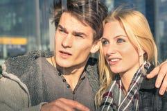 Jeunes couples dans l'amour derrière les réflexions en verre Photo libre de droits
