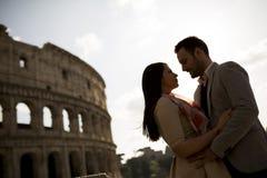 Jeunes couples dans l'amour devant le Colosseum à Rome Images stock