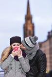 Jeunes couples dans l'amour embrassant et buvant la boisson chaude de c rouge Photo stock