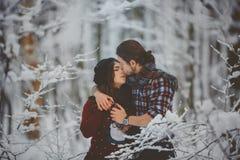 Jeunes couples dans l'amour embrassant dans la forêt d'hiver Image stock