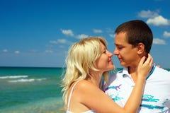 Jeunes couples dans l'amour embrassant sur la plage Photos stock