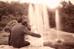 Jeunes couples dans l'amour en parc sur le fond de fontaine Photographie stock libre de droits