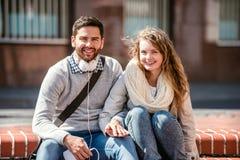Jeunes couples dans l'amour en ville se reposant sur des escaliers Images stock