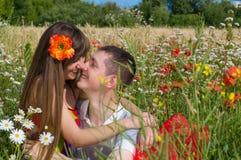 Jeunes couples dans l'amour et heureux parmi les fleurs dans le domaine Photo libre de droits