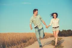 Jeunes couples dans l'amour extérieur Courses de couples à travers le champ Images libres de droits