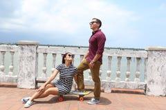 Jeunes couples dans l'amour extérieur avec la planche à roulettes Photos stock