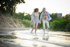 Jeunes couples dans l'amour fonctionnant par les mains de retenue d'eau Photos libres de droits
