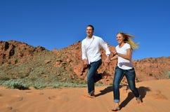 Jeunes couples dans l'amour fonctionnant sur la dune de sable Photo libre de droits