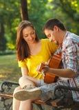 Jeunes couples dans l'amour jouant la guitare acoustique Photos libres de droits