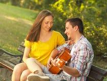Jeunes couples dans l'amour jouant la guitare acoustique Photographie stock