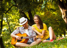 Jeunes couples dans l'amour jouant la guitare acoustique Images libres de droits