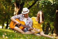 Jeunes couples dans l'amour jouant la guitare acoustique Photos stock