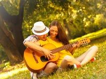 Jeunes couples dans l'amour jouant la guitare acoustique Photographie stock libre de droits