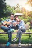Jeunes couples dans l'amour jouant la guitare acoustique en parc tandis que s Images stock