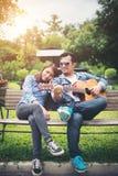 Jeunes couples dans l'amour jouant la guitare acoustique en parc tandis que s Photo libre de droits