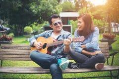 Jeunes couples dans l'amour jouant la guitare acoustique en parc tandis que s Photos stock
