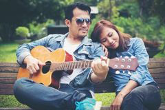 Jeunes couples dans l'amour jouant la guitare acoustique en parc tandis que s Photographie stock