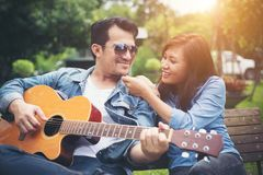 Jeunes couples dans l'amour jouant la guitare acoustique en parc tandis que s Image stock