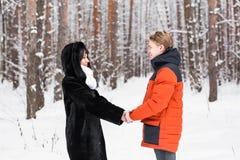 Jeunes couples dans l'amour jugeant des mains extérieures en hiver Image stock