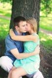 Jeunes couples dans l'amour, l'homme et la femme se reposant près de l'arbre Photos libres de droits