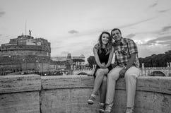 Jeunes couples dans l'amour, le mari et l'épouse, sur le pont en pierre du remblai de rivière du Tibre, contre le contexte d'Ange Images stock