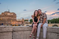 Jeunes couples dans l'amour, le mari et l'épouse, sur le pont en pierre du remblai de rivière du Tibre, contre le contexte d'Ange Images libres de droits
