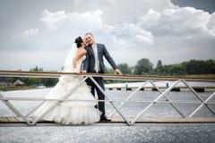 Jeunes couples dans l'amour les jeunes mariés avec un bouquet posant sur un pilier de fond avec des yachts Photos libres de droits