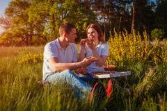 Jeunes couples dans l'amour mangeant de la pizza et causant dehors Femme et homme ayant le pique-nique romantique au coucher du s Photographie stock libre de droits
