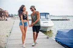 Jeunes couples dans l'amour marchant à la jetée de mer en bois Photo stock