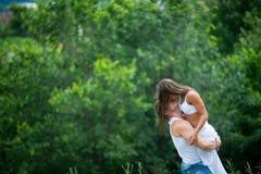 Jeunes couples dans l'amour marchant dans un pré Image stock