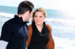 Jeunes couples dans l'amour marchant le long du bord de la mer Photo libre de droits