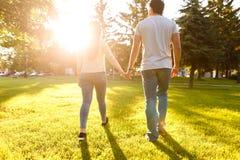 Jeunes couples dans l'amour marchant par le pré le jour ensoleillé Images libres de droits