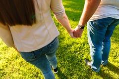 Jeunes couples dans l'amour marchant par le pré le jour ensoleillé Image stock