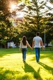 Jeunes couples dans l'amour marchant par le pré le jour ensoleillé Images stock