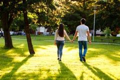 Jeunes couples dans l'amour marchant par le pré le jour ensoleillé Photos stock