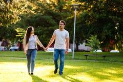 Jeunes couples dans l'amour marchant par le pré le jour ensoleillé Photos libres de droits