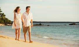Jeunes couples dans l'amour marchant sur la plage au coucher du soleil Photo stock