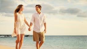 Jeunes couples dans l'amour marchant sur la plage au coucher du soleil Photos stock