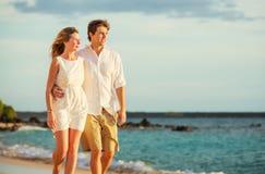 Jeunes couples dans l'amour marchant sur la plage au coucher du soleil Photos libres de droits