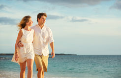 Jeunes couples dans l'amour marchant sur la plage au coucher du soleil Photographie stock libre de droits